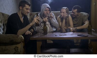Four young addicted people sitting in domestic interior on the sofa at night, drinking alcohol while man in hooded shirt smoking cannabis joint. Social issues, alcohol and drug abuse concept