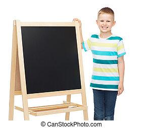 happy little boy with blank blackboard
