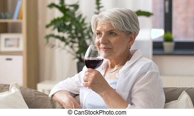 senior woman drinking red wine from glass at home - people,...