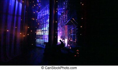 People and equipment are in illuminated offstage