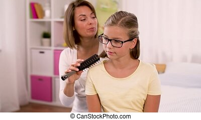 happy mother brushing daughter hair at home - people and...