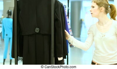 People and fashion, portrait of happy young woman smiling and trying out dress in clothing store