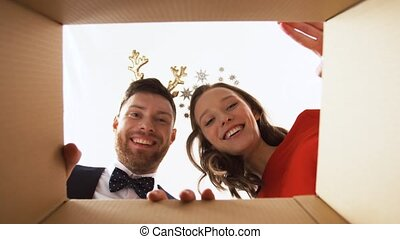 happy couple opening christmas gift box - people and...