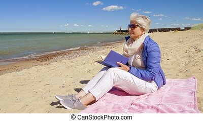happy senior woman reading book on summer beach - people and...