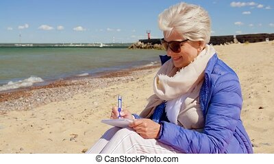 senior woman writing to notebook on summer beach - people...