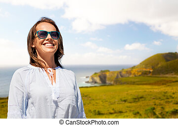 smiling woman in sunglasses over big sur coast