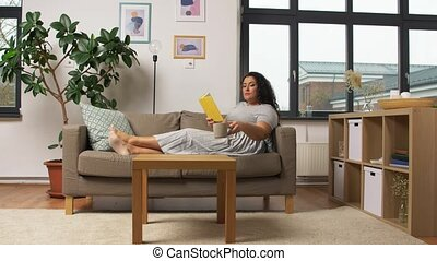 happy young woman reading book on sofa at home - people and ...