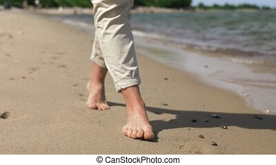 woman feet walking barefoot along summer beach - people and...