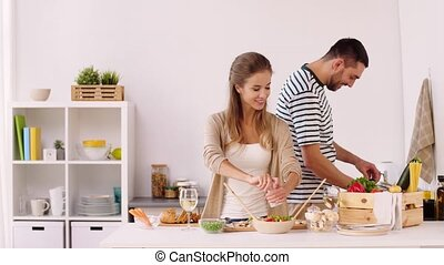 happy couple cooking food and having fun at home