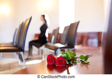 red roses and woman crying at funeral in church - people and...