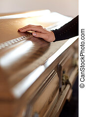 woman hand on coffin lid at funeral in church - people and...