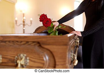 woman with red roses and coffin at funeral - people and ...