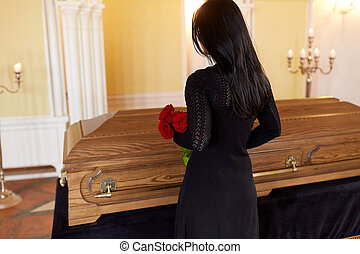 woman with red roses and coffin at funeral - people and...