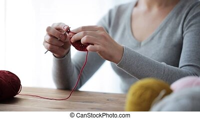 woman knitting with crochet hook and red yarn - people and ...