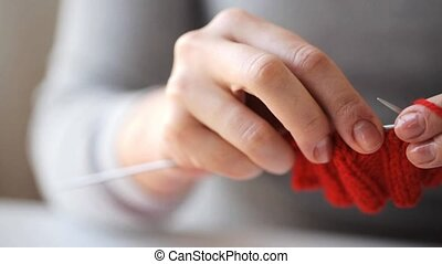 woman knitting with needles and red yarn