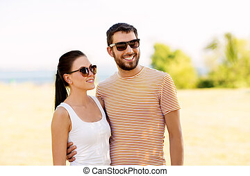 happy couple in sunglasses outdoors in summer