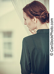 Alone woman looking through window waiting