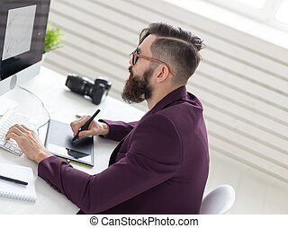 People and technology concept - High angle view of an artist drawing something on graphic tablet at the office