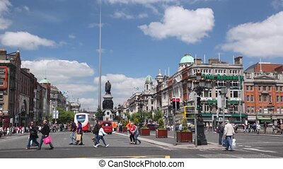 People and vehicle traffic on very wide O'Connell Street in Dublin