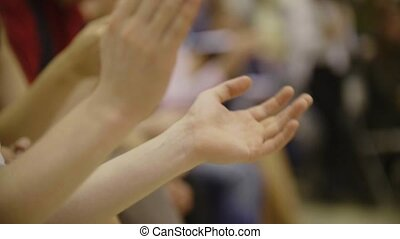 People applaud - close-up of clapping hands of sitting people on dancing event
