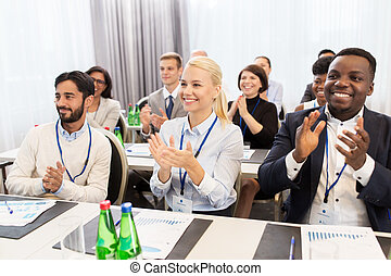 people applauding at business conference