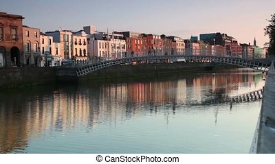 People are crossing the Ha'penny Bridge, there are many cars moving along the other bank, Dublin, Ireland.