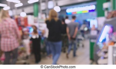 People are shopping in a supermarket, defocused blurred...