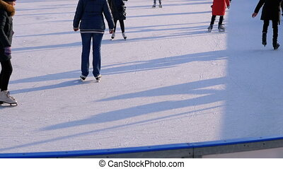 People are Skating on Ice Rink in the Sunny Day. Many people...