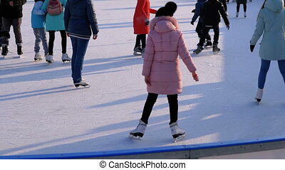 People are Skating on Ice Rink in the Sunny Day. Slow Motion