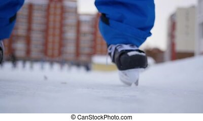 People are skating on the open skating ring on a cloudy day in winter in blurring