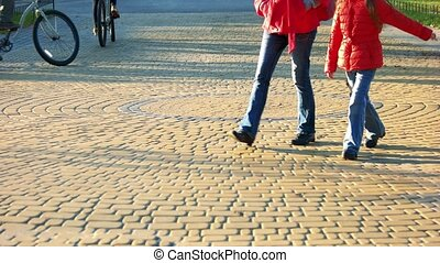 People are strolling on cobblestone pavement.