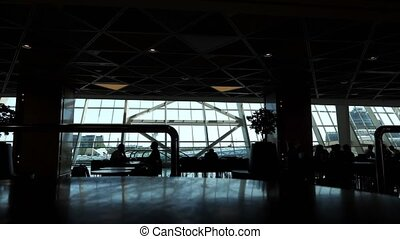 Silhouettes of people in cafe in airport terminal with panoramic windows.