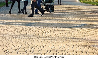 People are walking on cobblestone pavement.