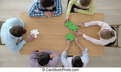 People assembling puzzle