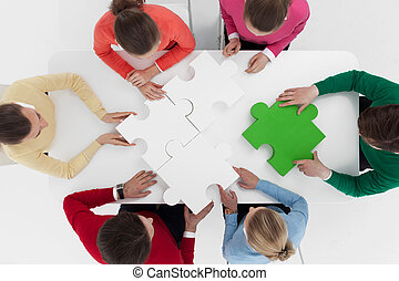 People assembling puzzle - Group of people assembling jigsaw...