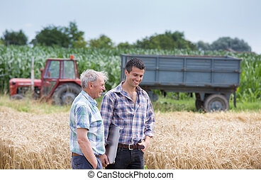 People at harvest - Two farmers talking on wheat field...
