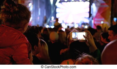People at Music Concert Recording Video on Smartphones. Fan person filming concert party on phone. Crowd cheering at music event with flashing light show. 4K.
