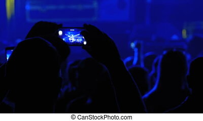 People at Music Rock Concert Taking Photos or Recording Video with Smartphones