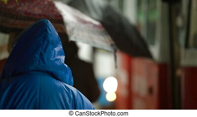 People at rainy bus stop