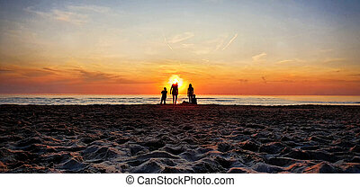 People at the beach during golden sunset