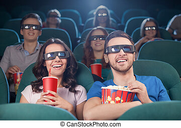 People at the cinema. Cheerful people in three-dimensional...