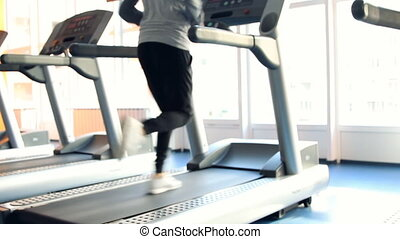 People at the gym exercising. Run on a machine. Out of focus