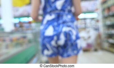 People at the supermarket, blurred background. buyers choose...