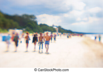 People at the weekend walk on the beach in summer. Blurry