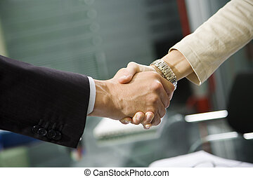People at work: man and woman hand shaking at a meeting