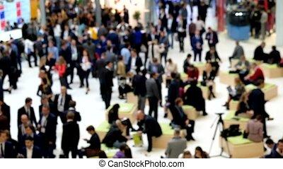 People attend international exhibition. Blurres
