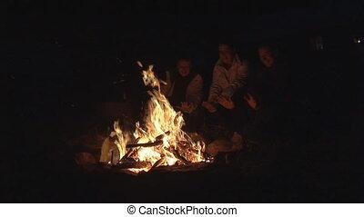 people basking on bonfire - three people sitting at bonfire...