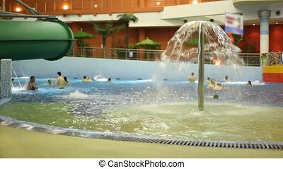 People bathe in pool with fountain in water park