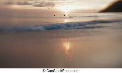 People bathing in sea. Seasurf on sunset at Nai Harn beach on Phuket island. Thailand. Lens Baby Sweet 35mm.