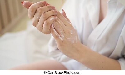 people, beauty, cosmetics and bodycare concept - beautiful woman applying moisturizing hand cream at home bedroom